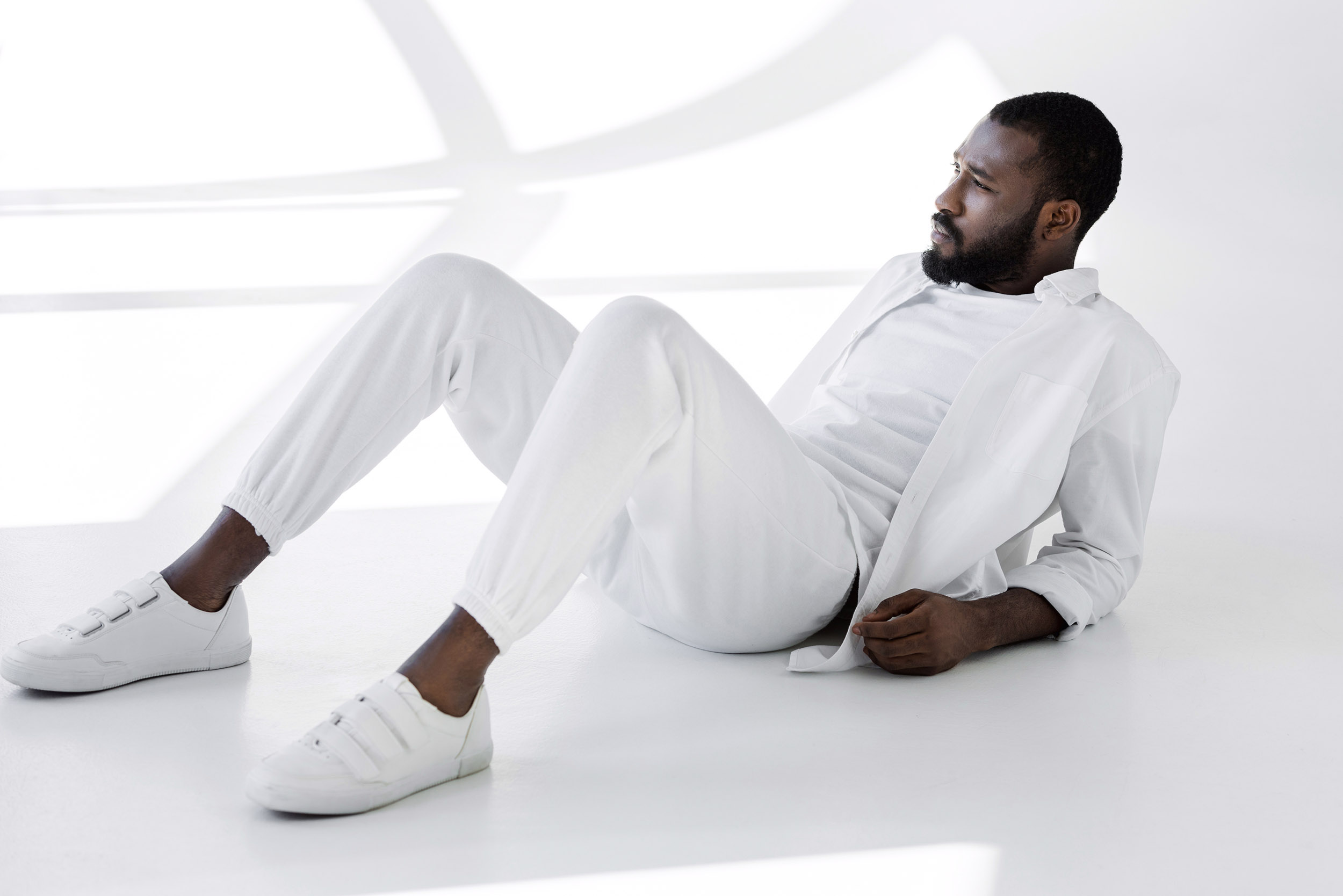 Handsome African American man dressed in all white sitting on an all white floor